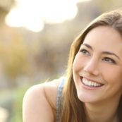 Woman with white teeth thinking and looking sideways